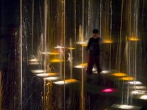 Fountain of light. Young boy in fountain at night stock image