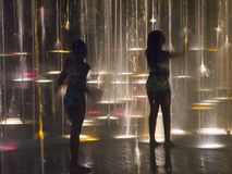 Fountain of light 2. Two sisters in a fountain at night royalty free stock images
