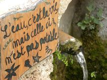 Fountain with message in Saint-guilhem-le-desert, a village in herault, languedoc, france. Fountain with message in Saint-guilhem-le-desert, a village in herault stock image