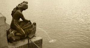 Fountain metallic sculpture and lake in sepia tone Stock Photos