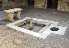 Fountain and mosaic floor in Roman house in Parco Archeologico di Ercolano. Pictured is a fountain, bench and mosaic floor in a Roman house in the Parco Stock Photos