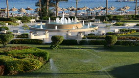 The fountain near beach at the luxury hotel and lawn irrigation Royalty Free Stock Image