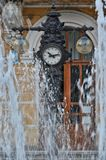 Fountain near an old clock. In the old city center Royalty Free Stock Images