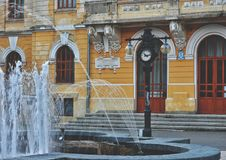 Fountain near an old clock royalty free stock photography
