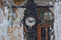 Fountain near an old clock. In the old city center Royalty Free Stock Photos