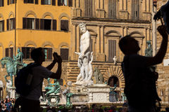 Fountain of Neptune with silhouettes of tourists making photo in Florence Stock Photo