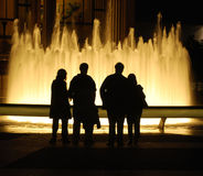 Fountain at night. Four people in silhouette looking at a brightly lit fountain at night time Royalty Free Stock Photo