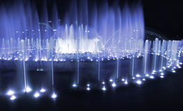 Fountain night blue. Urban night scene: illuminated by blue light fountain in a park in Moscow (Russia) by evening or night with streetlamps at the background Royalty Free Stock Images