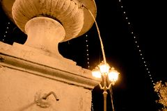 A fountain at night with water coming down and the light of a lamp on the street stock photography