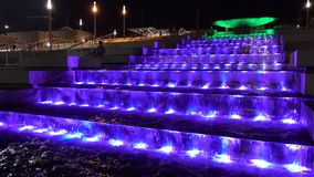 Fountain at night. The water flows down the stairs with light. stock video footage