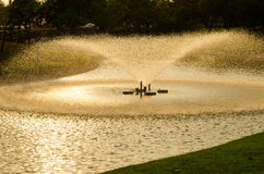 Fountain in the park reflect the evening sun. Royalty Free Stock Photo