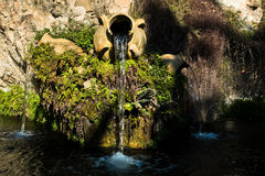Fountain in a park with water flowing from an old amphora, Cagliari, Sardinia Stock Images