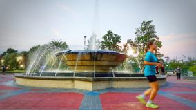 Fountain in the park and women jogging. Stock Photos