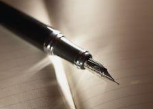 Fountain pen. Black fountain pen on notebook royalty free stock photos