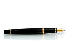 Fountain Pen. A classic, gold-nibbed black fountain pen, reflected on a white surface royalty free stock images