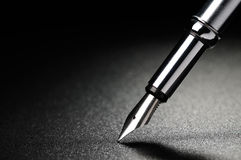 Fountain pen. Old fountain pen on a black textured background Stock Image