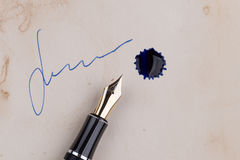 Fountain pen with blots. Fountain pen lying on old paper with blots royalty free stock image