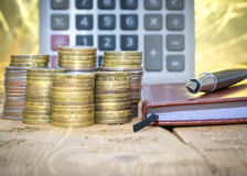 Fountain pen,calculator, coins and notebook on a wooden table. Royalty Free Stock Photos