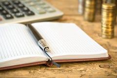 Fountain pen,calculator, coins and notebook on a wooden table. Stock Photos