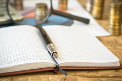 Fountain pen,calculator, coins and notebook on a wooden table. Royalty Free Stock Photography
