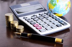 Fountain pen and calculator money coins stack and earth for Busi royalty free stock photos