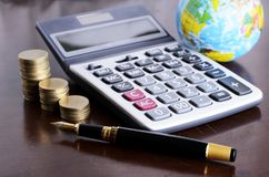 Fountain pen and calculator money coins stack and earth for Busi Stock Images
