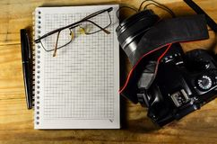 Fountain pen, camera, glasses, and notebook on a wooden table. Fountain pen, modern camera, glasses, and notebook on a wooden table Stock Image