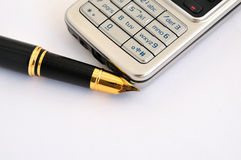 Fountain pen and cellphone. Golden and back fountain pen and gray cellphone Stock Images
