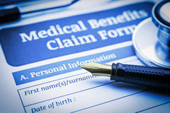 Fountain pen, a chest-piece of a stethoscope and a medical benefits claim form on a clipboard. Stock Photo