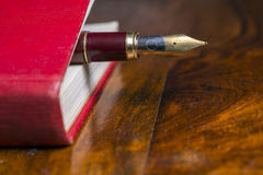 Fountain pen. Closeup of fountain pen on a red book on a wooden table Royalty Free Stock Photo