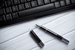 Fountain pen and computer keyboard Stock Photo