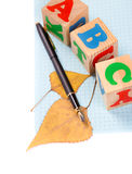 Fountain pen, cubes with letters and autumn leaves Royalty Free Stock Photography