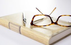 Fountain pen and glasses on book Stock Photo