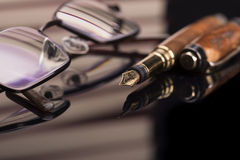 Fountain pen and glasses. Fountain pen and reading glasses and a black glossy surface royalty free stock image