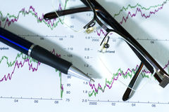 Fountain pen and glasses on stock chart. Fountain pen and glasses on stock chart on blue report. Shot in studio royalty free stock photography