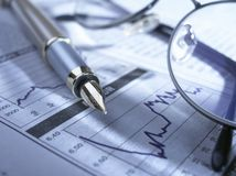 Fountain pen and glasses on stock chart Royalty Free Stock Photography