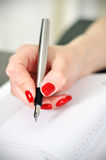 Fountain pen in hand Royalty Free Stock Image