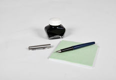 Fountain pen with ink bottle and notepad Stock Images