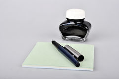 Fountain pen with ink bottle and notepad Stock Photos