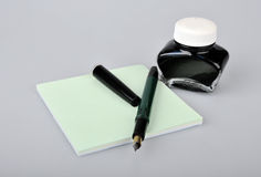 Fountain pen with ink bottle and notepad Royalty Free Stock Images