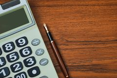 Fountain pen or ink pen with calculator on wooden working table royalty free stock images