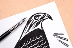 Fountain pen with ink drawing hawk. Stock Image
