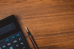 Fountain pen or ink pen with calculator on wooden working table Stock Images