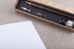 Fountain pen and ink set with white sheet. On textured background Royalty Free Stock Photography