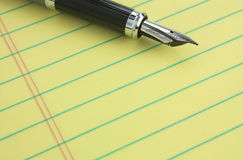 Fountain pen on legal pad. Fountain pen on yellow legal pad of paper - add your business message Royalty Free Stock Image