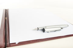 Fountain pen lying on blank paper Stock Image