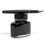 Fountain pen lying on the ink bottle Stock Image