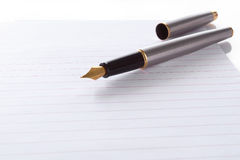 Fountain pen lying on page in a spiral bound notep Royalty Free Stock Image