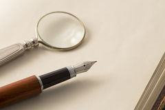 Fountain pen and the magnifying glass Stock Images