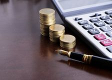Fountain pen and Money coins stack and calculator for finance co stock photography